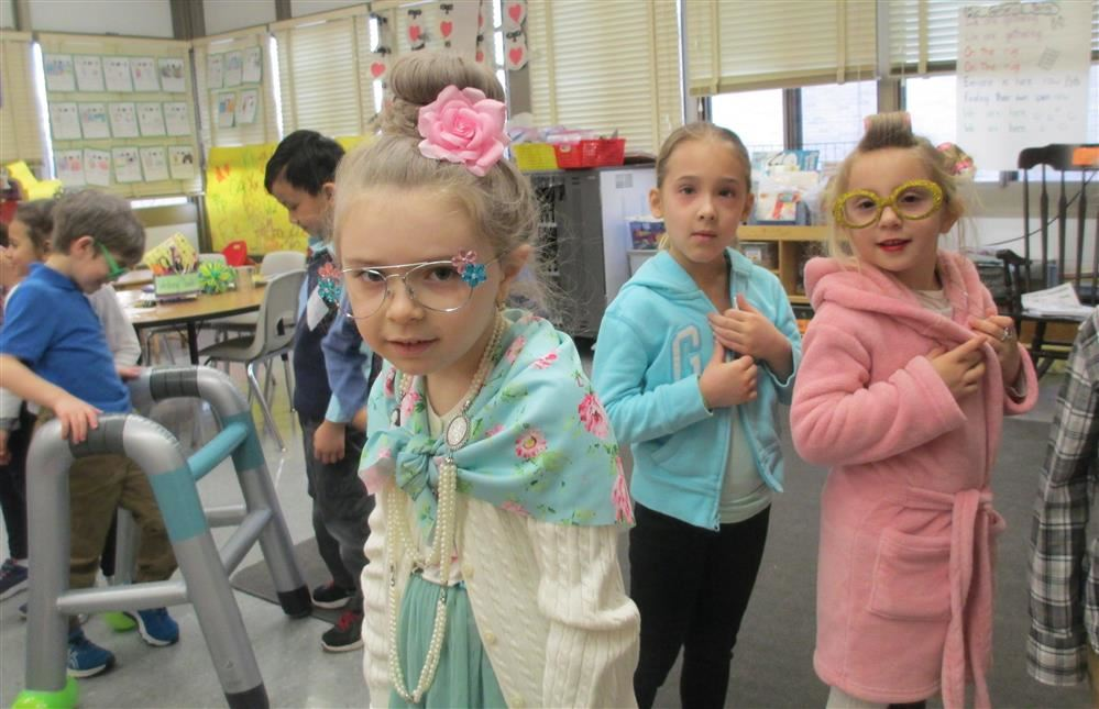 Two kindergarten girls smiling, dressed as 100 year old ladies for The 100th day of School!