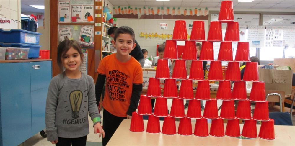 Two smiling kindergarteners pose next to a pyramid tower of red cups that they built
