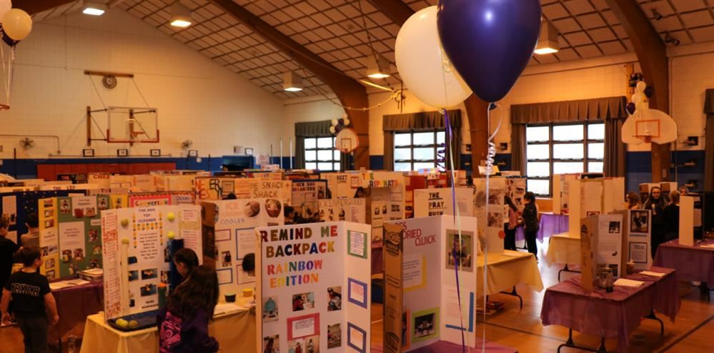 Many booths set up in the school gym displaying student science fair projects
