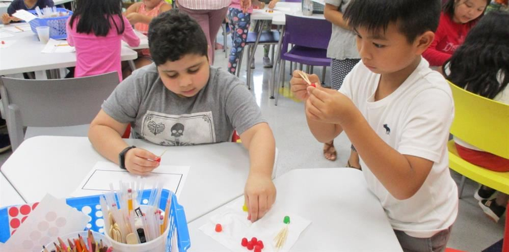 Two boys constructing a tower with toothpicks and gumdrops