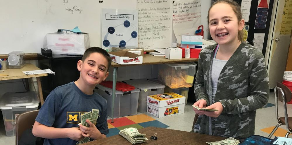 Two students count dollar bills in a classroom