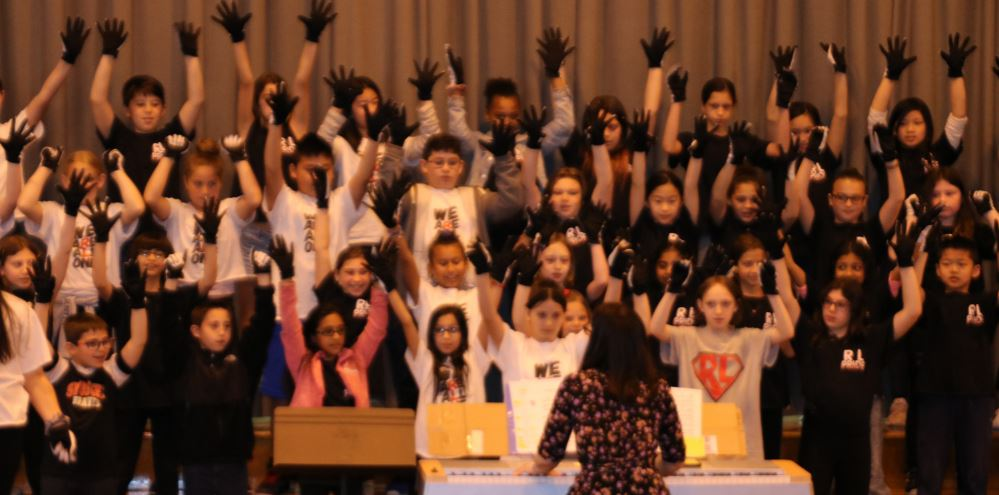Action shot of chorus students performing with their hands reaching up.