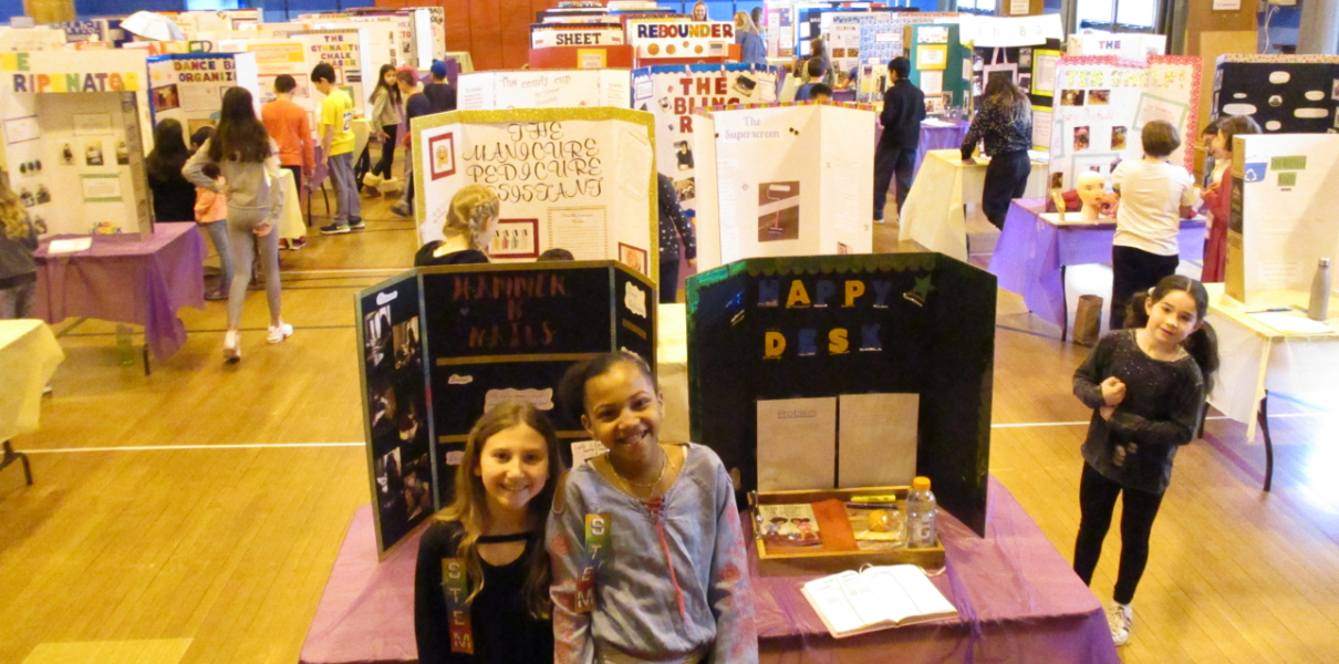 Two students smiling in front of their STEM Fair project display