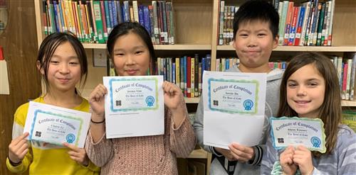 A group of students holding up coding certificates