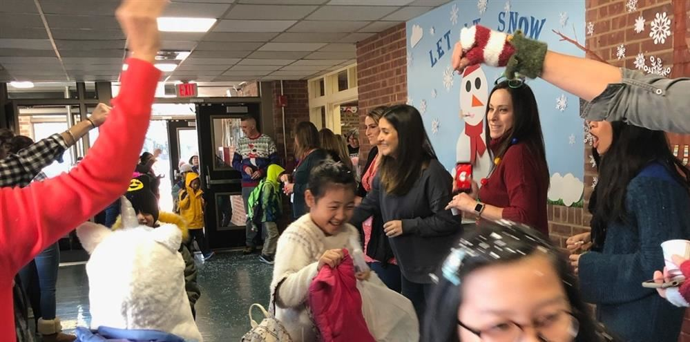 Teachers are putting fake snow on children as they arrive at school.