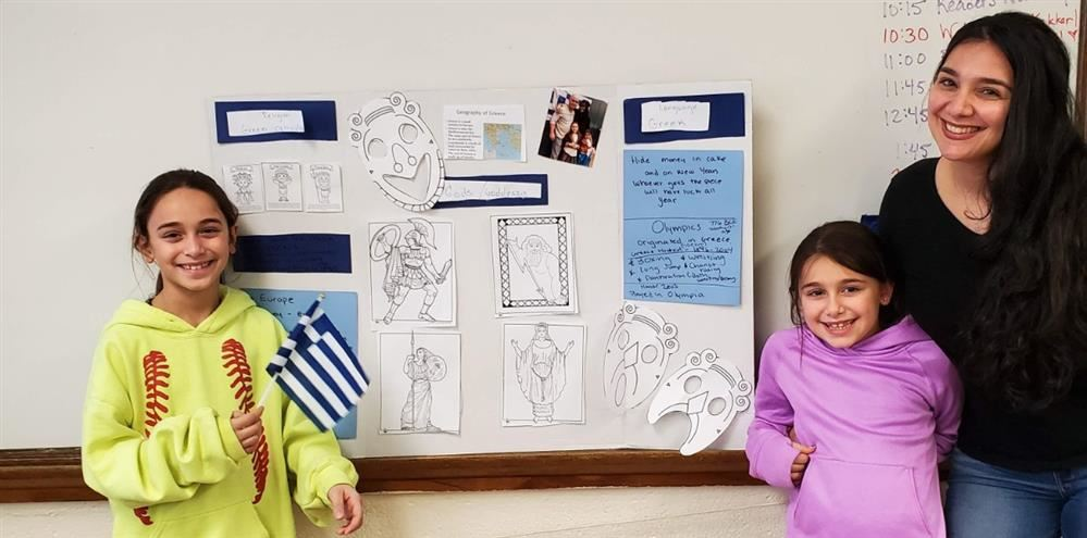 A mother and her 2 girls are showcasing a tri-fold poster about Greek Culture