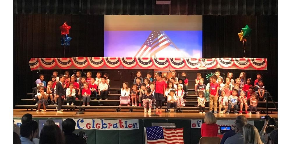 A large group of kindergarten students are on stage, ready to perform. They are all dressed in red,
