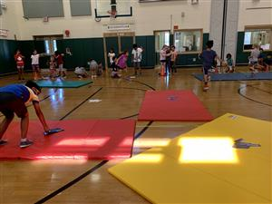 The gym has colorful mats and children.