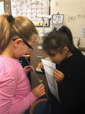 Two girls are using a mirror to read a secret message.