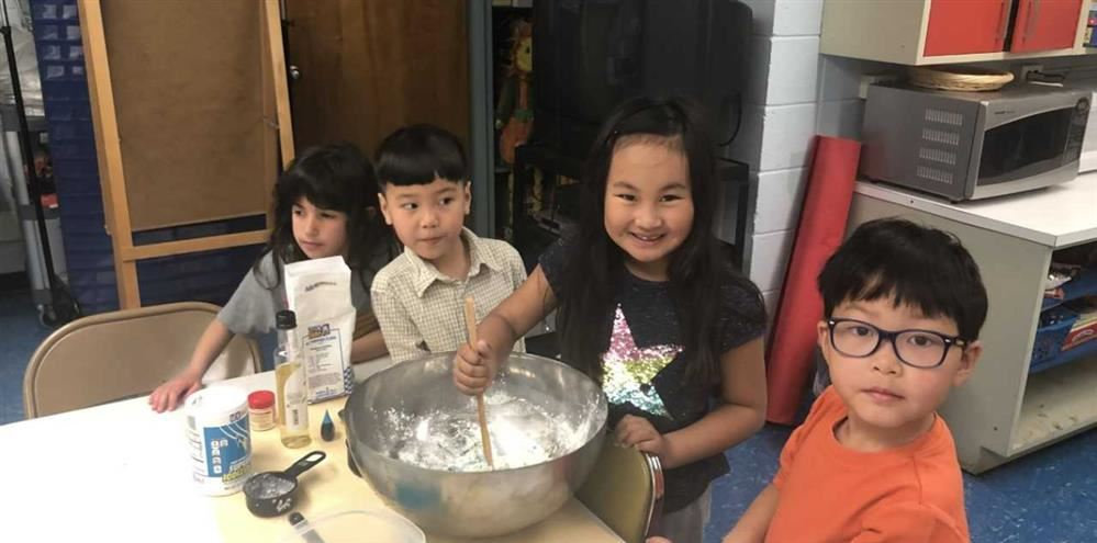Four young students are mixing flour in a bowl to create homemade playdough.