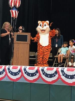 Grover, a tiger mascot, waves form the stage.
