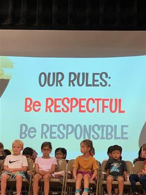 School rules are displayed behind cildren: Be respectful and Be responsible.