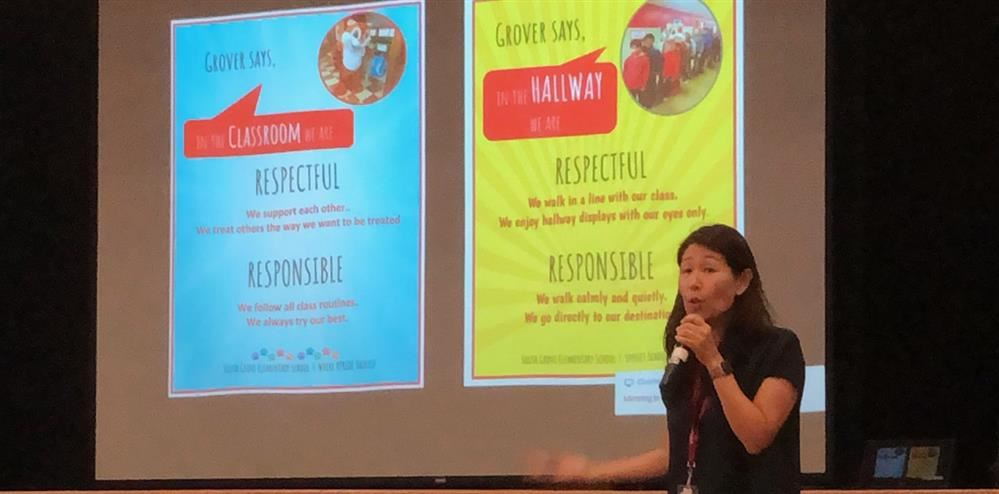 The principal, Ms. An, is speaking in front of a project display of character education posters.