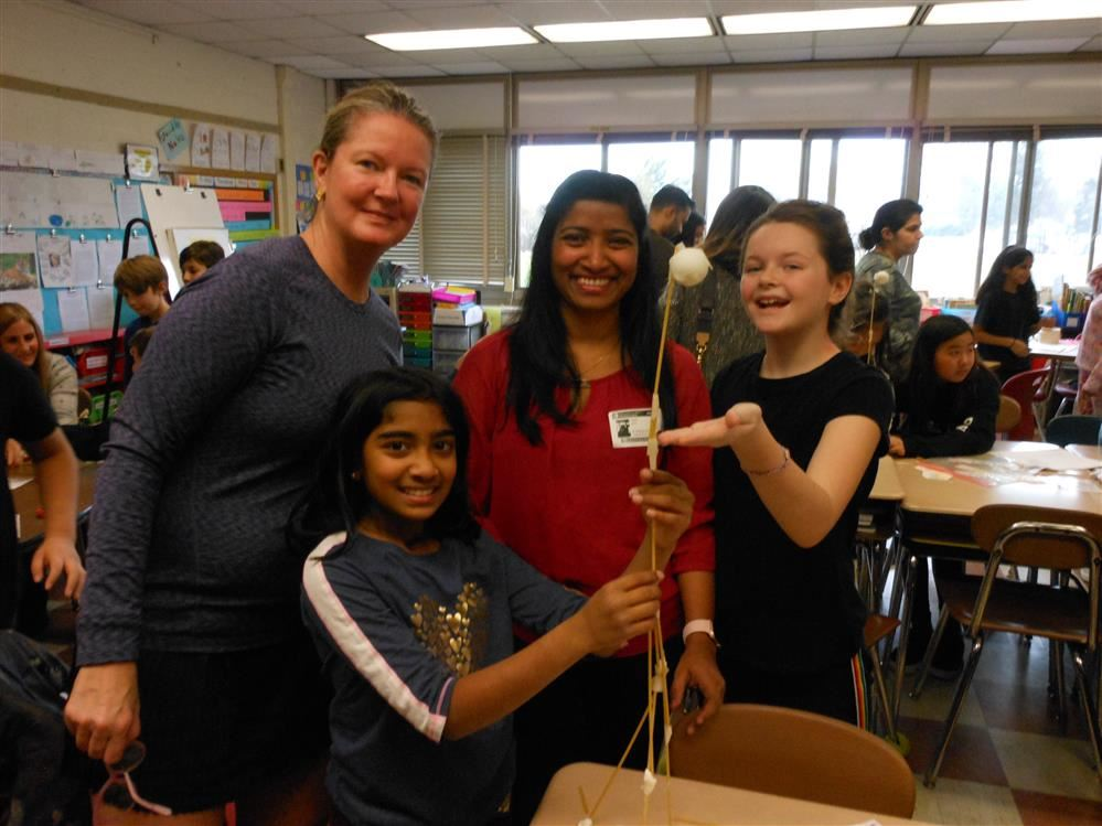 Two fifth grade girls and their mothers showcase a tower made out of spaghetti, marshmallows and tap