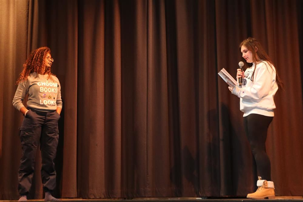 A student speaking on stage to an author