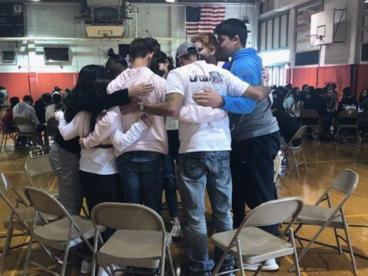 A group of students huddle together on Junior Day