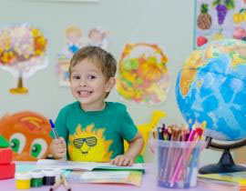 Child at a desk with a globe and art supplies