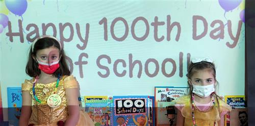 Two first graders standing in front of a sign that says Happy 100th Day of School.