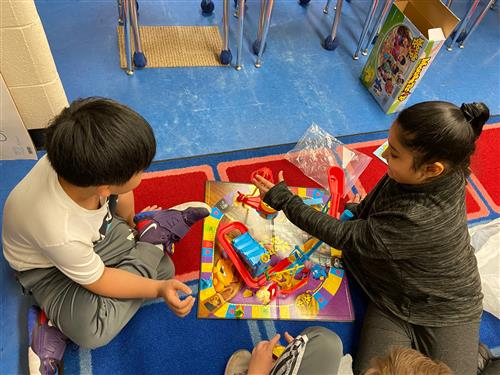 2nd graders playing a board game.