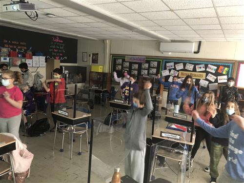 Students dancing to a virtual assembly.