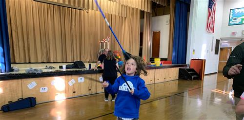 A third grader throwing up a blue devil stick.