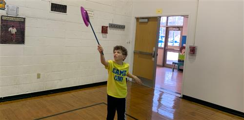 A third grader spinning a plate on a stick.