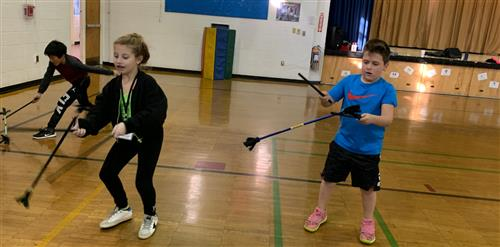 Third graders playing with devil sticks.