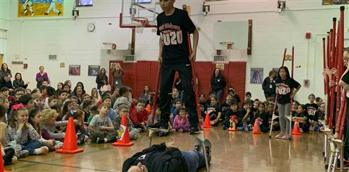 A stilt walker, walking over Mr. Snyder.