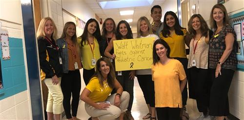 12 teachers holding a sign that says... Walt Whitman Fights Against Pediatric Cancer.