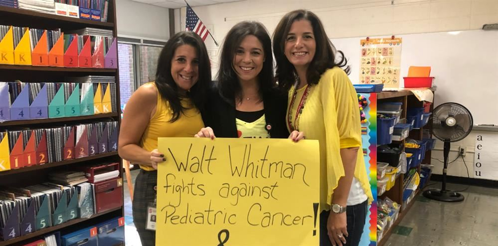 Three teachers holding a sign that says... Walt Whitman Fights Against Pediatric Cancer.