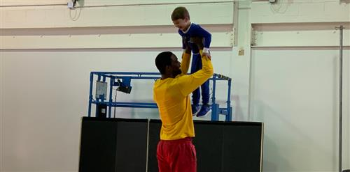 A tall basketball player holding a kindergartner in the air.