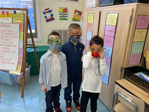 Three first graders wearing 100 day of school masks.