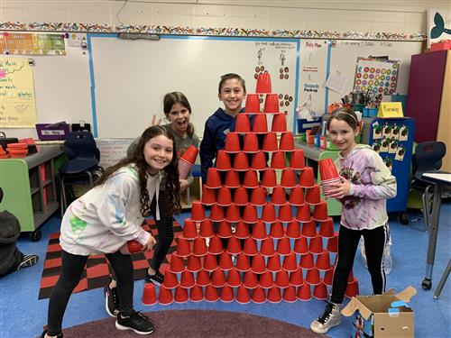 Fourth Graders making a pyramid out of cups.