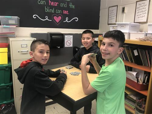 Fifth graders playing cards.