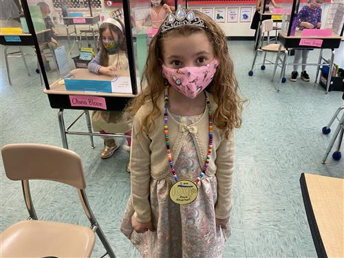 A first grader wearing a 100 day medal around her neck.