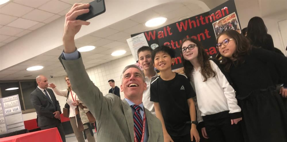 Dr. Rogers is taking a selfie with four members of the Walt Whitman Ambassadors
