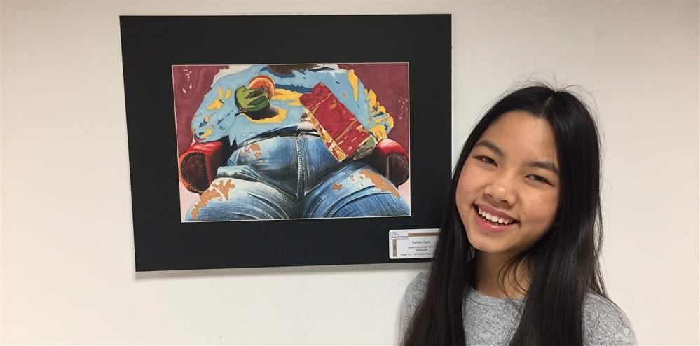 Student Kaitlyn Hom poses with her winning artwork